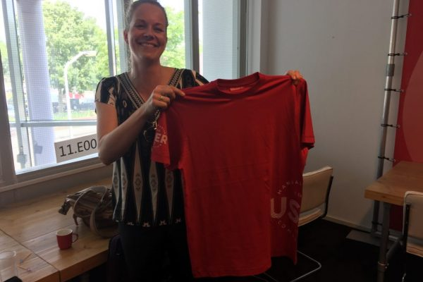 Het MUC t-shirt omhoog gehouden door ontwerpster Christel Zevenbergen-Ruysink